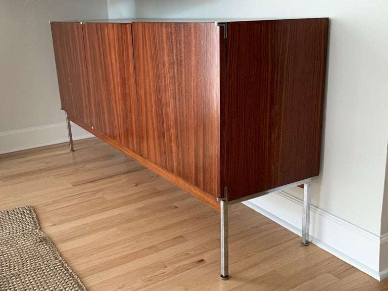 Stunning credenza, sideboard, cabinet, rendered in exquisite rosewood on the exterior case and contrasting light wood interior with 3 doors, 2 of which open to a compartment with a shelf, the left door opens to find 4 gray felt lined drawers. This