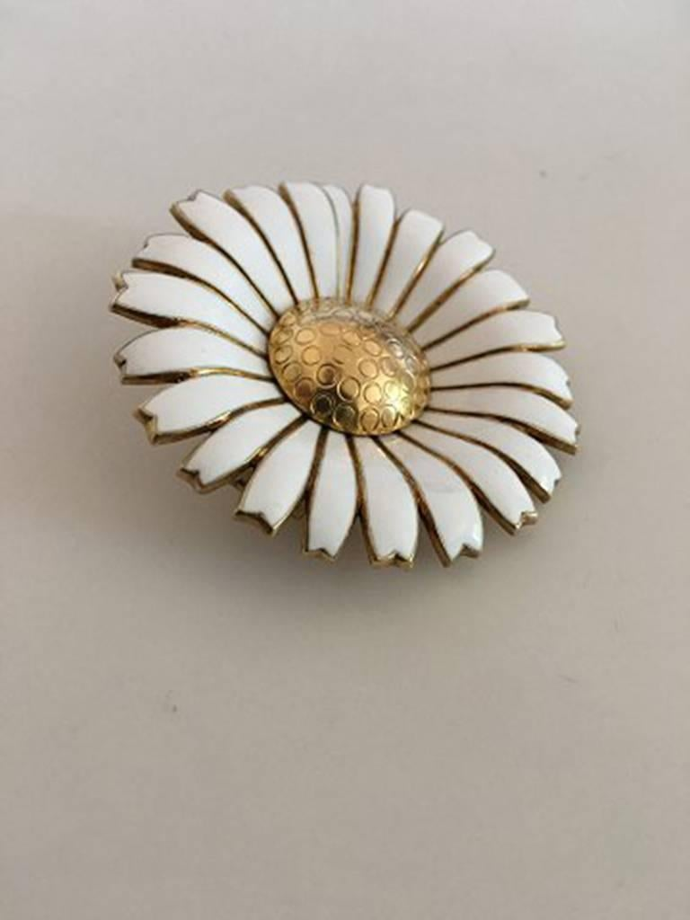 Anton Michelsen Daisy Brooch in Gilded Sterling Silver and White Enamel. Measures 5 cm / 1 31/32 in. Weighs 31.2 g / 1.10 oz. In nice condition