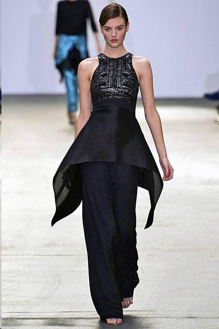 Stunning Antonio Berardi beaded peplum gown in a slender sculptured silhouette. Fashioned of black silk crepe with racer style bodice embellished with beads and crystals. The gown is paneled with a taffeta peplum and organza back panel. Fully lined
