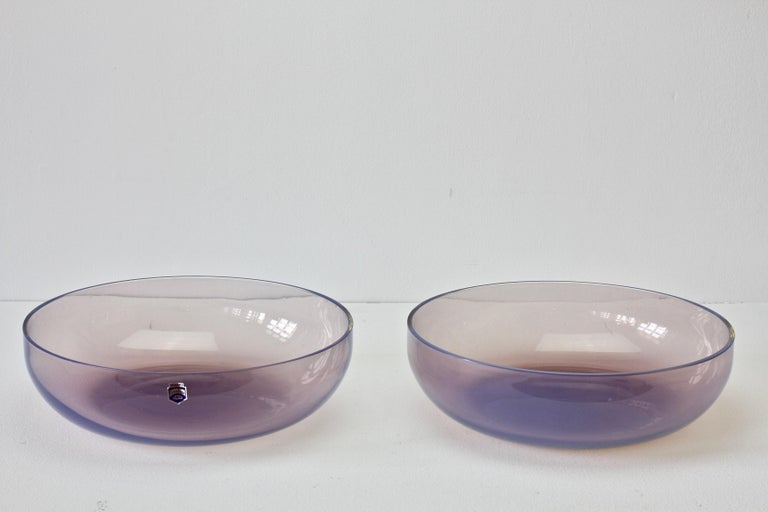 Large pair of pink / aubergine colored 'Opalino' Murano glass serving / center bowls designed by Antonio da Ros (1936-2012) for Cenedese, circa 1970-1990. Wonderful translucent color of pink or aubergine, almost pink sapphire to purple amethyst.