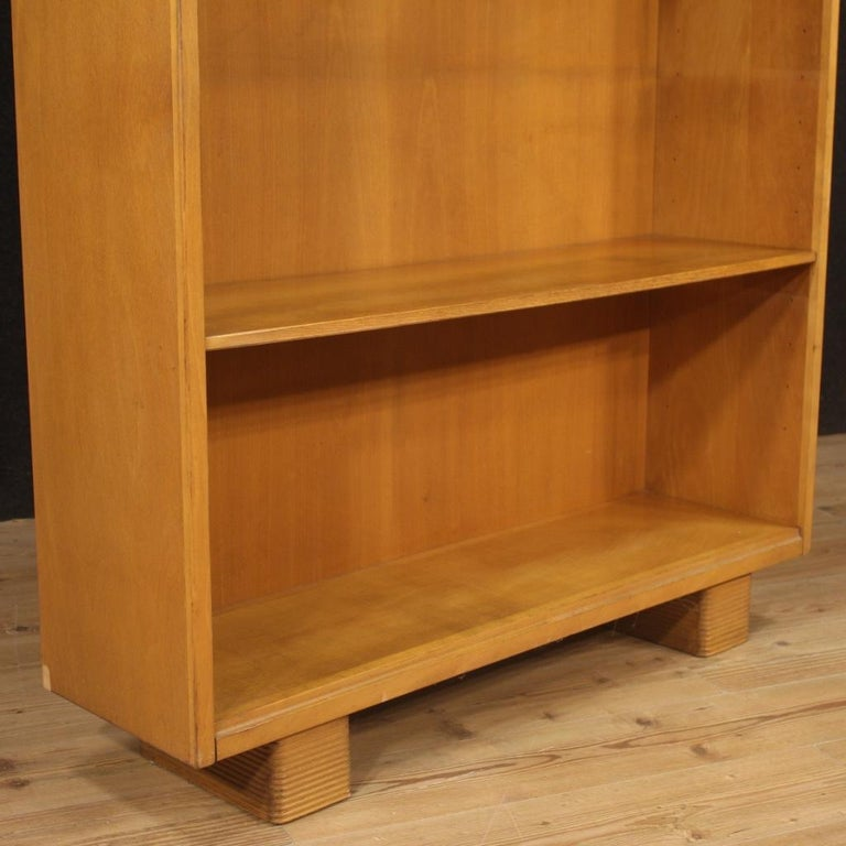 Italian design bookcase from the first half of the 20th century. Furniture carved in beech wood and fruitwood produced by the company Antonio Ferretti of Milan born in 1904. Bookcase equipped with two shelves that can be positioned at various