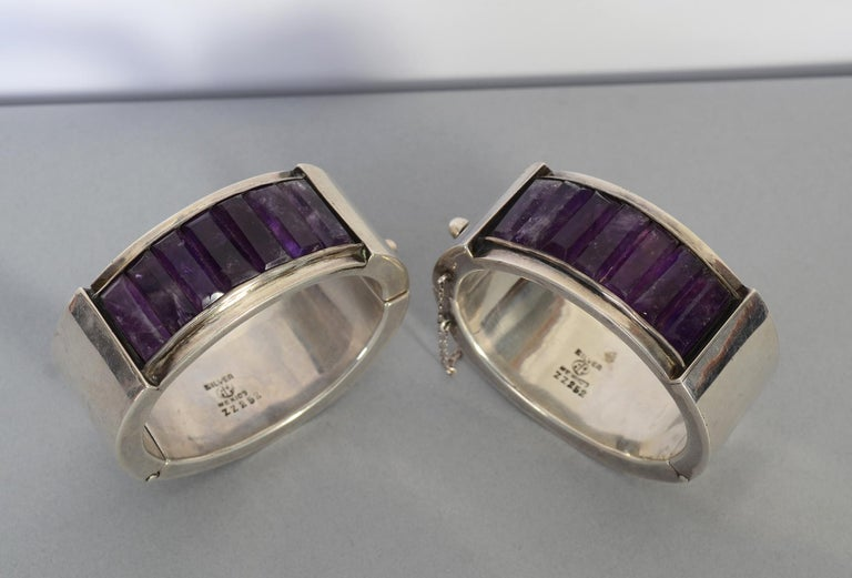 This is a stunning and unusual pair of early Antonio Pineda bangle bracelets made of sterling silver and amethyst. Both bracelets have Antonio's mark used between 1941 and 1949. They measures 1 3/16