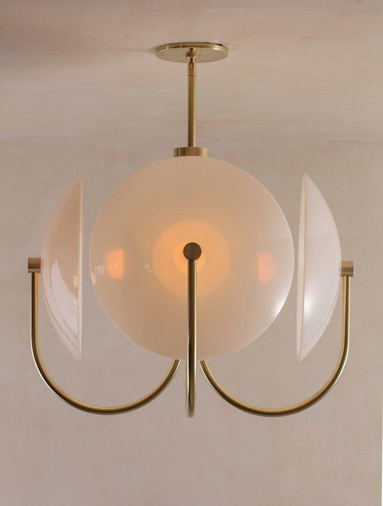 The Aperture series was created to provide a beautiful quality of light by combining bounce and ambient glow. The light source is held in a hand-spun perforated brass dome on one side, while a hand-bent tube arcs around the other; Diffusing and