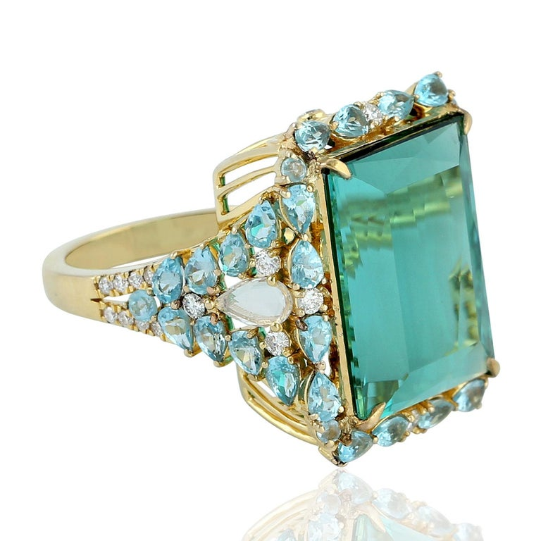 Beautiful Apetite Tourmaline and Diamond Ring set in 18K Yellow Gold. This ring is truly special as the blue color of tourmaline is so rare with brilliant princess cut.  Ring Size: 7  ( can be sized )  18KT: 7.507gms Diamond: 0.49cts APETITE: