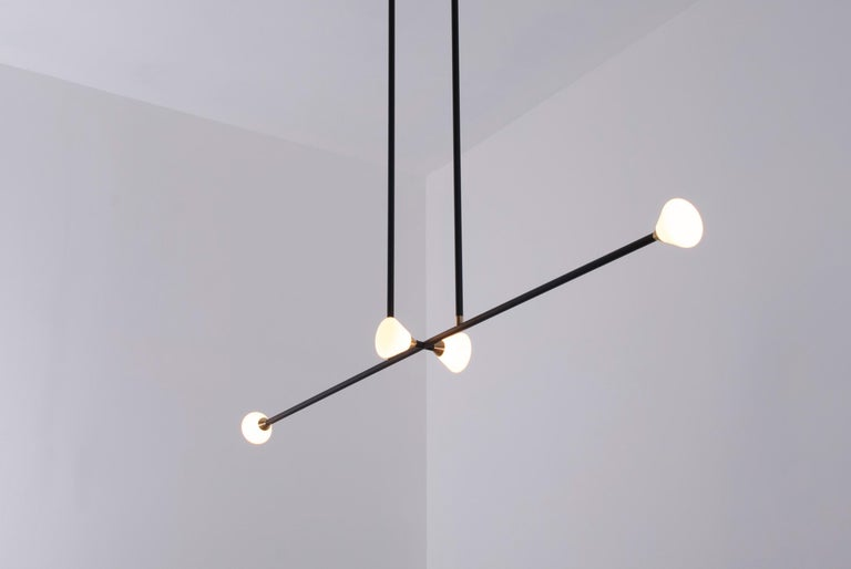 Opaque glass and brass shades seamlessly blend into a matte black armature. The Apollo four features four triangular shades in a balanced, double-stemmed luminary. The chandelier features a blackened oak canopy.  Our Apollo series chandeliers house