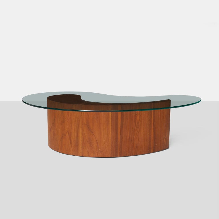 A coffee table with walnut base shaped like an apostrophe and a 1'2? glass top, attributed to Vladimir Kagan.