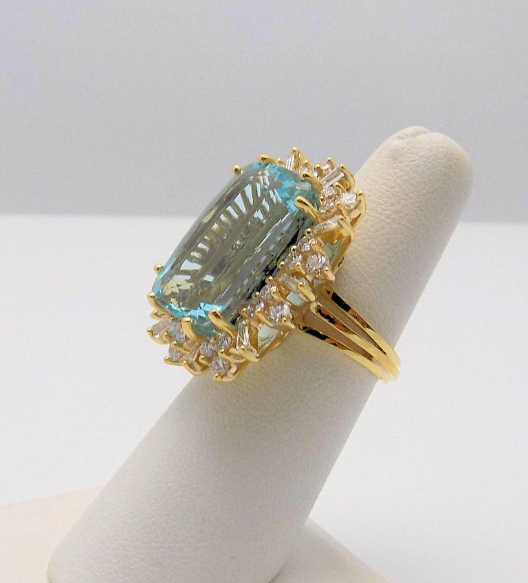 18 Karat Yellow Gold Ring, 1 Cushion Cut Aquamarine 25.67 Carat; 30 Round Brilliant Diamonds, 10 Tapered Baguette Cut Diamonds 2.00 Carat Total Weight; VS-SI, H-I; Finger Size 6.5; 11.4 DWT or 17.72 Grams.