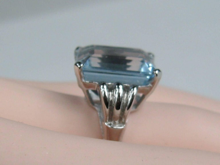 Simply stunning on this 14K White Gold Emerald Cut Aquamarine Engagement Ring. Large 13.75 Carat Octagonal cut aquamarine set in 14K white gold. Step Cut. Color Greenish Blue. Stone measures 14.85 x 14.06 x 9.37 Per GIA report. The ring is a size