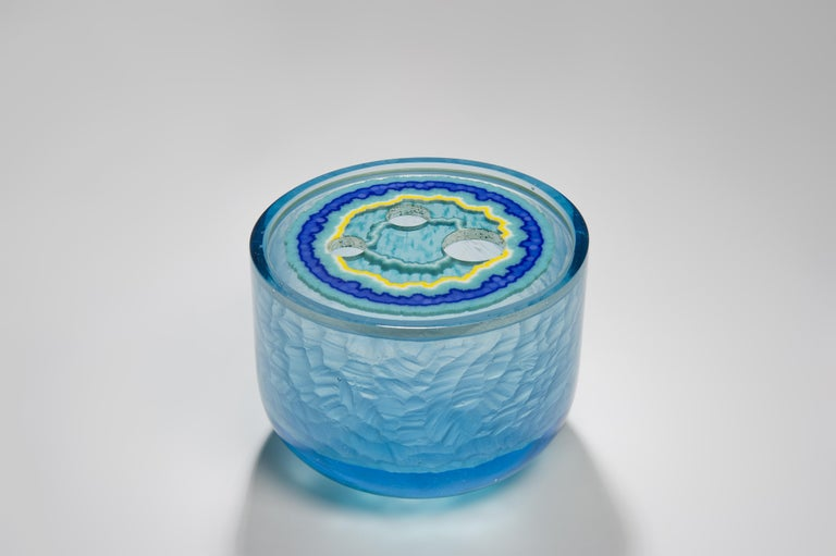 Aquamarine Agate Geode is a unique aqua, turquoise, blue and yellow sculptural piece created from cast glass by the British artist Angela Jarman. Using the lost wax technique, the base is cast pale blue lead crystal. The top disc insert is created