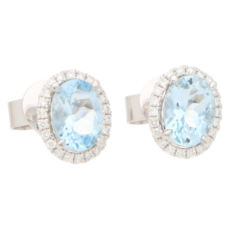 A lovely pair of aquamarine and diamond oval halo earrings set in 18k white gold.  Each earring centrally features a beautiful blue colored oval shaped aquamarine surrounded by a halo of 22 round brilliant-cut diamonds. All of the stones are set to