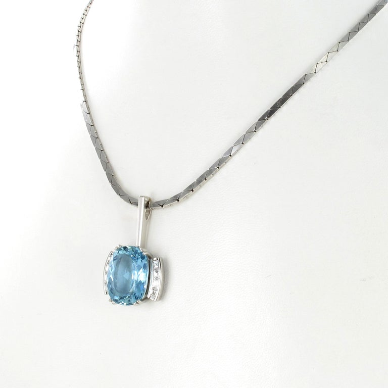 This beautiful necklace features a cushion shaped aquamarine of approximately 10.70 carats, arfully set in a mounting of platinum 950. Accented by 8 trapezoidal cut diamonds of G/H colour and vs clarity, total weight approximately 0.80