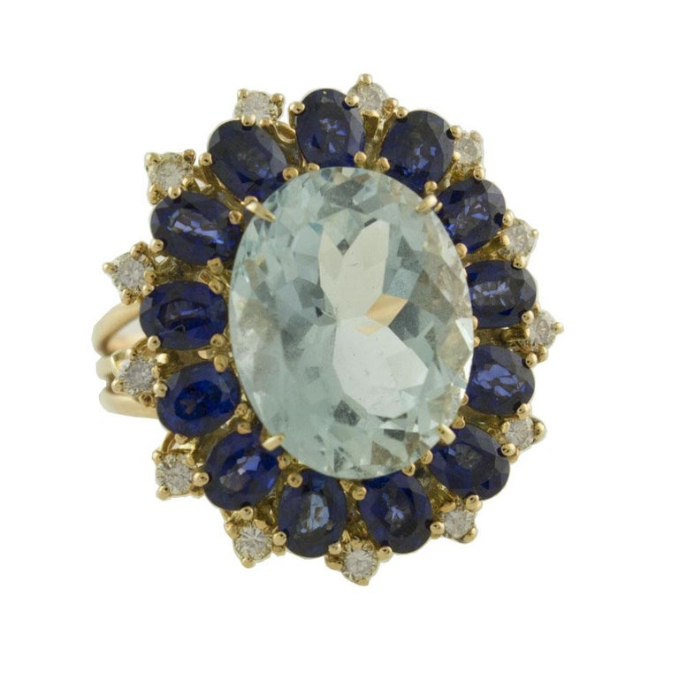 Gorgeous ring in 14K rose gold composed of a refine and intense light blue aquamarine in the center surrounded by blue sapphires crown and white diamonds detailes Diamonds 0.39 ct  Blue Sapphires 2.74 ct  Aquamarine 6.52 ct    1.4 cm X 1.1 cm  Total
