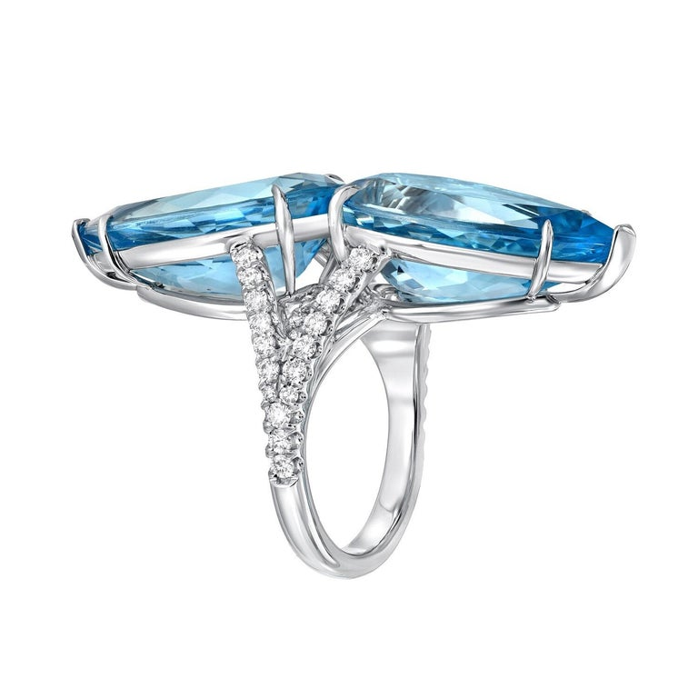 Incredible pair of vivid blue Aquamarine pear shapes, weighing a total of 18.59 Carats, and a total of 0.80 carats of round brilliant diamonds, are set together to compose this magnificent hand crafted platinum cocktail ring. Size 6. Resizing is