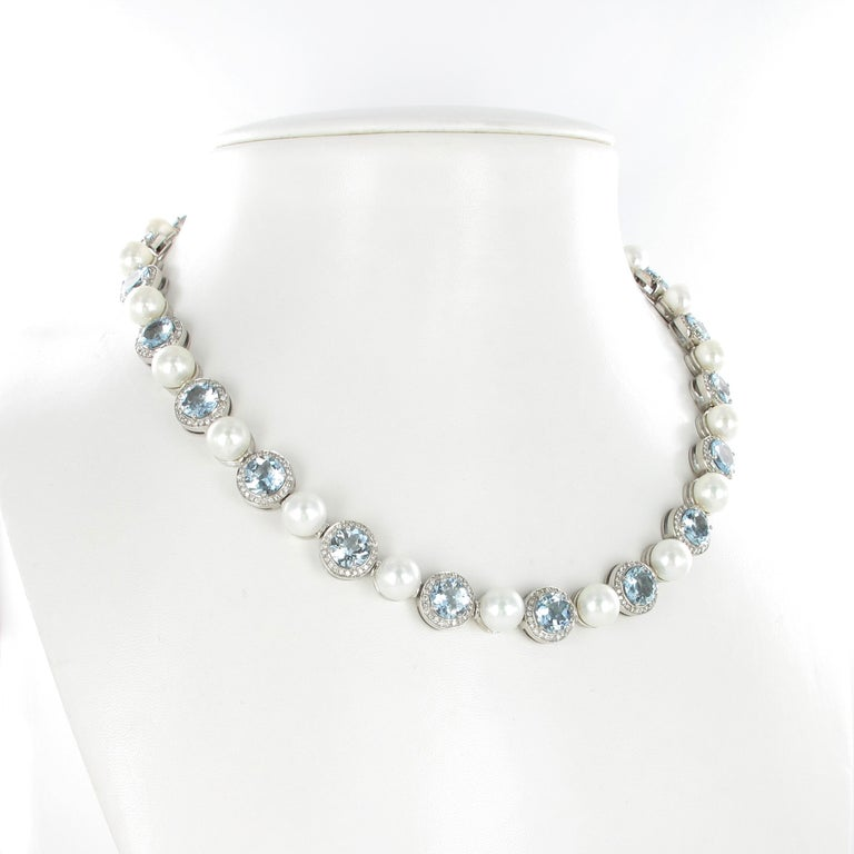 This neat necklace is designed as 21 round elements, each set with a light blue round cut aquamarine surrounded by white brilliant cut diamonds. Connected with 20 Japanese Akoya cultured pearls of 9.0 mm in diameter. The perfectly round pearls