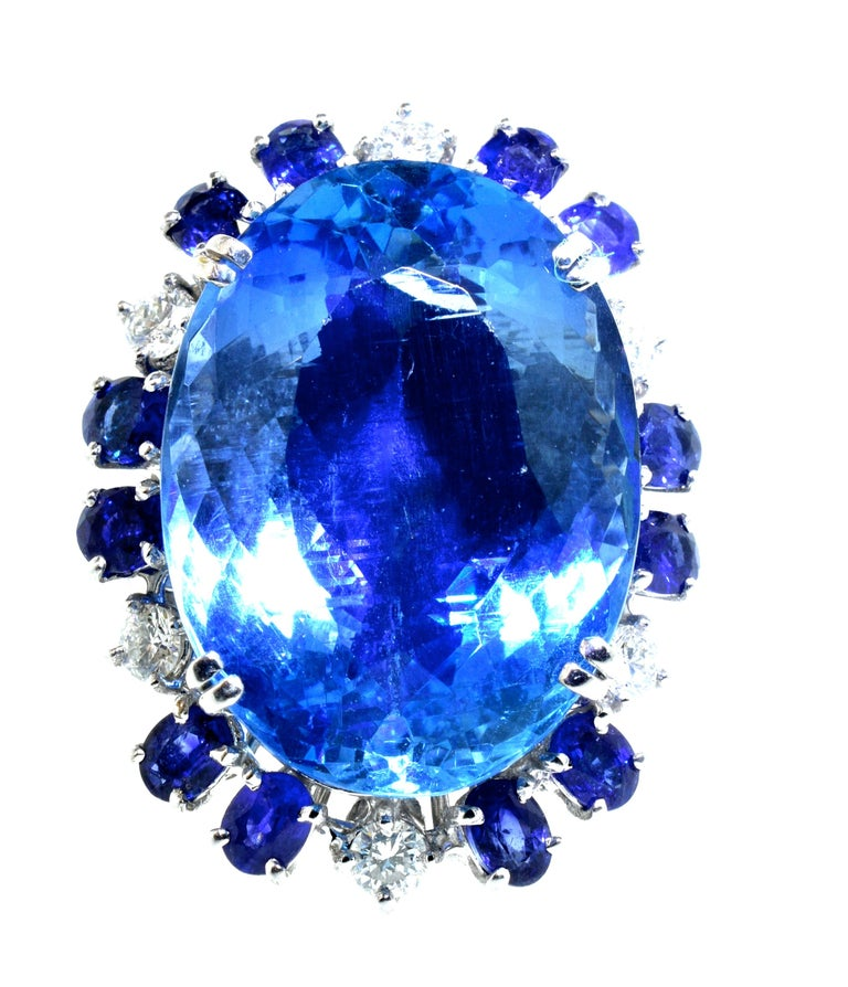 Natural  Aquamarine weighing approximately 25 cts.  It is large and beautiful displaying a fine blue color.  Surrounding this center stone are 12 fine natural medium natural unheated and untreated blue sapphires.  The sapphire weigh is approximately