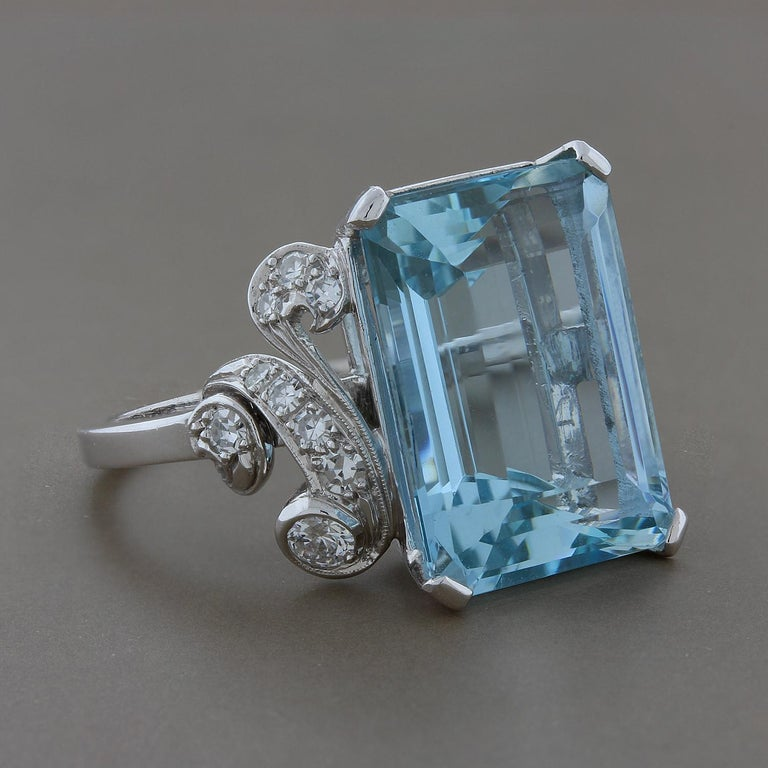 A lovely cocktail ring featuring a 12.48 carat aquamarine set in a platinum mounting. There are 0.30 carats of round cut diamonds accenting the emerald cut aquamarine, set in platinum. Size 7 ¾