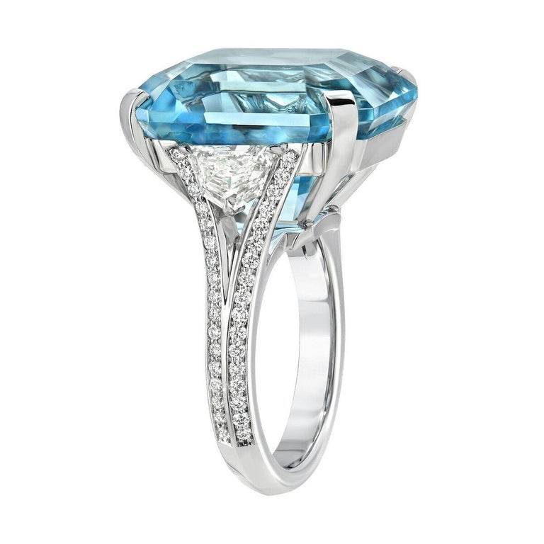 This superbly cut  20.37ct emerald cut Aquamarine, is flanked by a pair of F/VS2 Epaulet diamonds, weighing a total of 0.96ct and a total of 0.41ct round brilliant diamonds, all hand set in a magnificent platinum cocktail ring.  Crafted by extremely