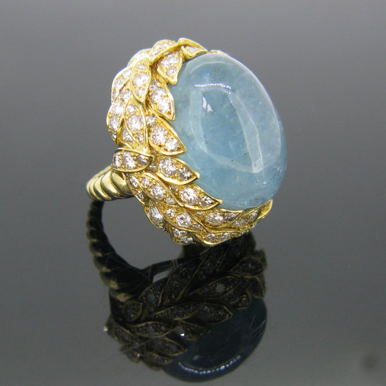 This bold and impressive ring features an incredible 40 carat cabochon cut aquamarine. The aquamarine is set within a nest of 42 leaves motifs with diamonds. There are 141 diamonds set all around the aquamarine on the leaves. The band is made in