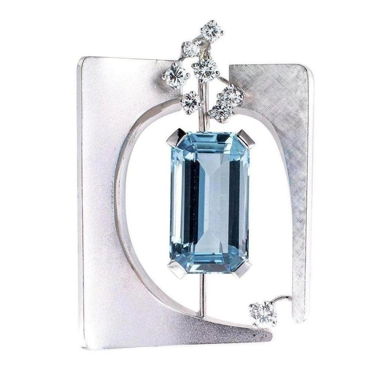 Aquamarine diamond and white gold brooch pendant circa 1960. The design showcases an emerald-cut aquamarine weighing approximately 11.00 carats within an open, modernist  florentine and matt finished white gold frame decorated by randomly placed