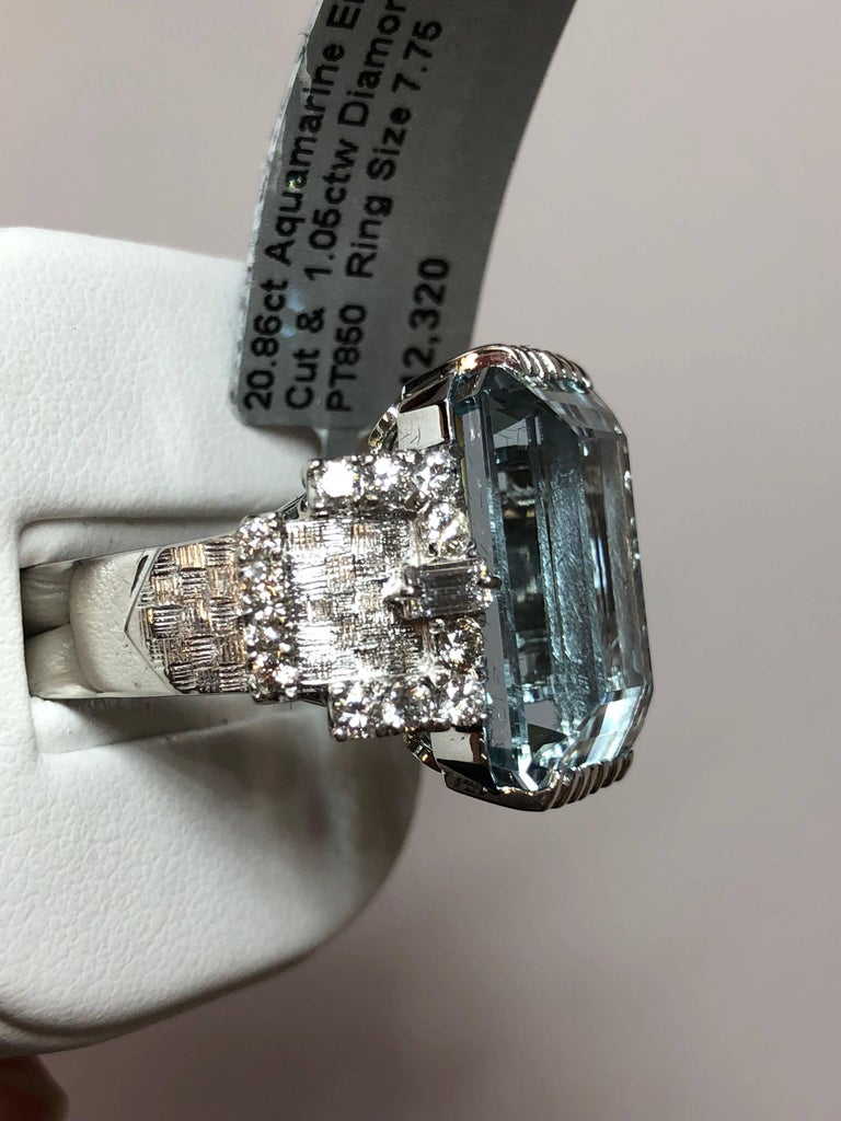 Lovely 20.86 carat aquamarine emerald cut surrounded by 1.05 carats of white diamonds in a platinum mounting.  This cocktail ring is a showstopper and perfect for any occasion! Size 7.75.