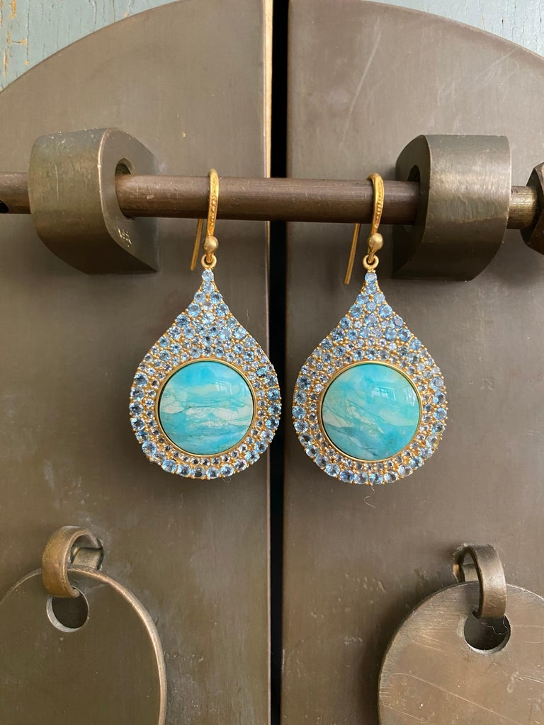 Designed by award winning jewelry designer, Lauren Harper, these earrings have 3.93cts of stunning faceted Aquamarines that surround beautiful ocean-toned Petrified Opalized Wood pieces in a perfect teardrop shape. You will find these earrings match