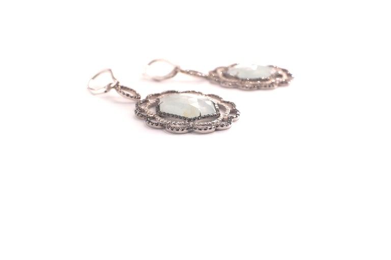 Nastasia Hexagon Aqua Diamond Eardrops A pair of platinum, aquamarine, black and white diamond eardrops, each composed of a hexagonal aquamarine rose-cut as the center.  Around this gemstone, one finds a fine black diamond frame, followed by two