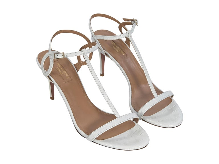 Product details:  White croc-embossed leather sandals by Aquazzura.  Adjustable ankle strap.  T-strap design.  Open toe.   Condition: Pre-owned. Very good. Est. Retail $ 650.00