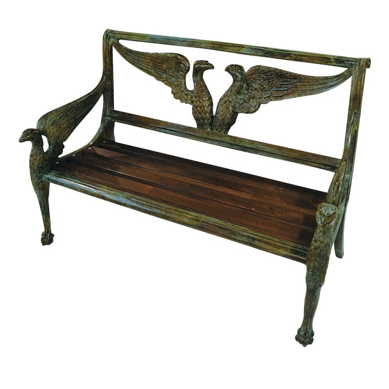 This exquisite bench features a seat in wood and a structure magnificently executed in bronze using the lost-wax technique. The two front legs are in the shape of an eagle portrayed in profile with its wings spread backwards to form the armrests.