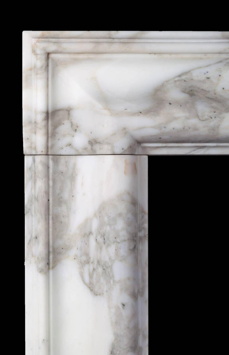 A classic bolection fireplace with moulded frame on plain square plinths, carved from three solid pieces of marble with mason mitred corners. Made by Ryan & Smith from a beautiful block of Arabscato Carrara marble sourced in Italy.