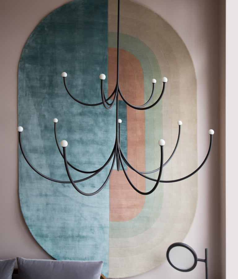 Arca is a lighting system whose form is a play of contrasts between the classical swooping branches and the spare minimalism of its linear, black composition. Tiers can be easily added together to create a unique chandelier. LED/CRI 90 lighting.