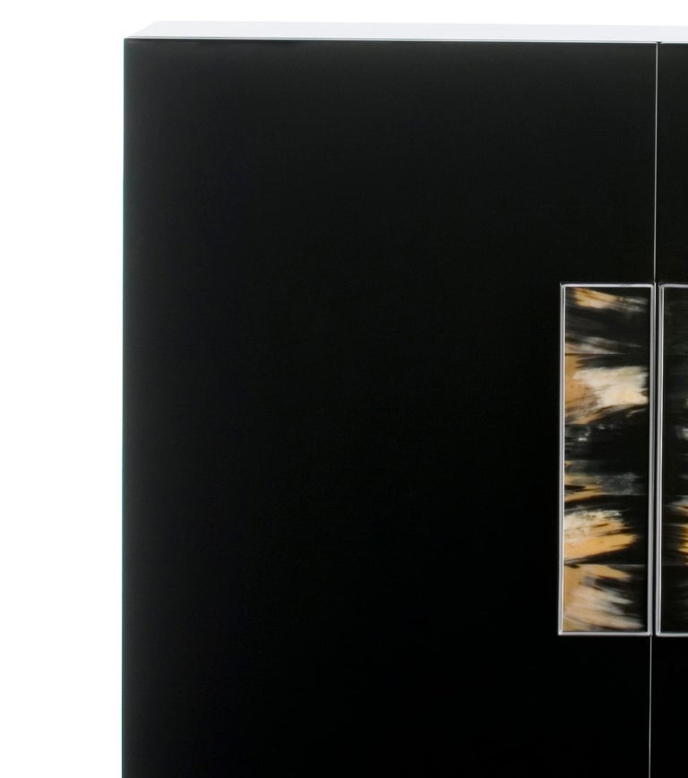 Vertical 2-door cabinet in wood with lacquered black gloss finish and chromed brass handles with dark horn inlays. Interior: 4 shelves in tempered smoked glass.  Overall dimensions: W 135 x D 55 x H 142 cm.