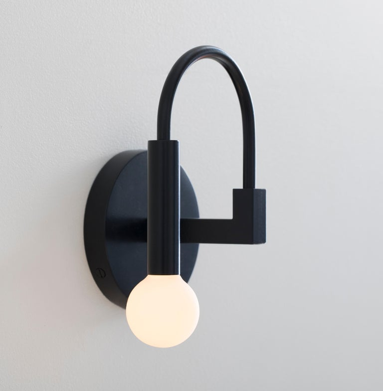 Arch  Arch draws on the elemental forms of Roman architecture to create a playful yet timeless sconce, blurring the line between traditional and contemporary design.  Details: This listing is for one arch wall sconce in matte black with satin