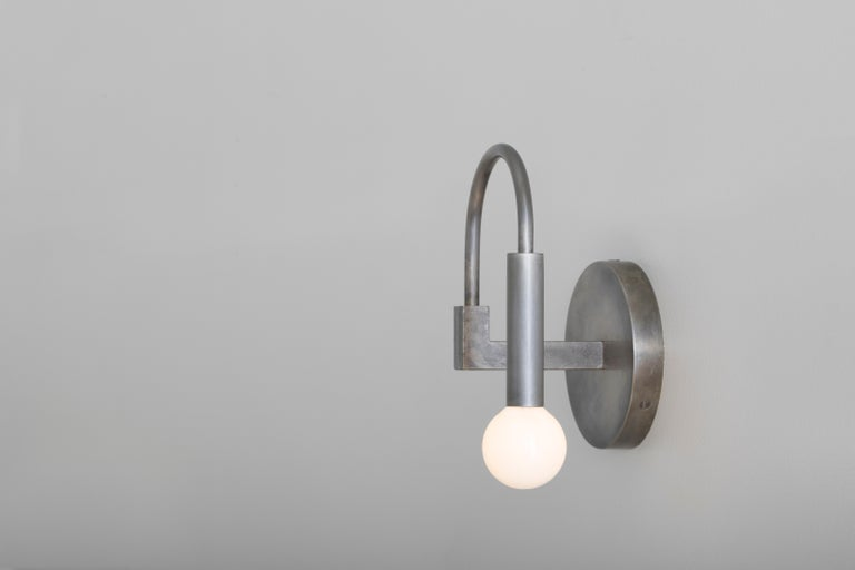 Arch  Arch draws on the elemental forms of Roman architecture to create a playful yet timeless sconce, blurring the line between traditional and contemporary design.   Details This listing is for one arch wall sconce in Vintage Silver with satin