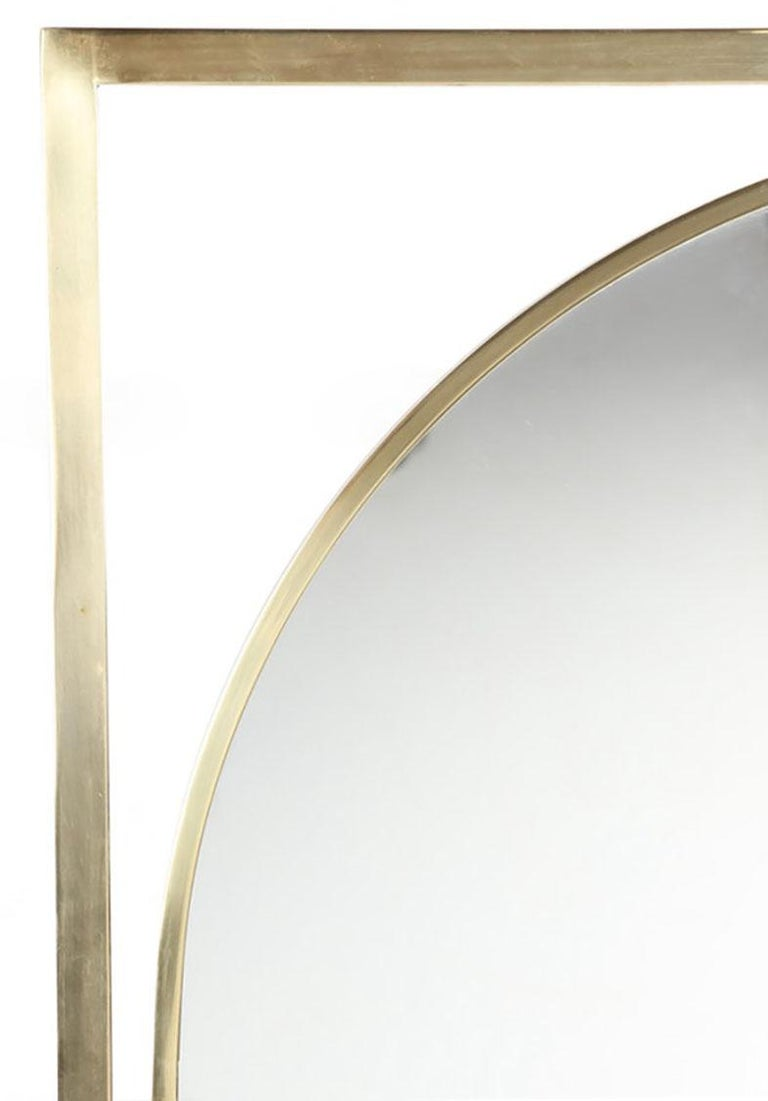 Uncommon large brushed brass square stock framed mirror floating inside a brushed brass square stock open frame, possibly midcentury Italian. The arched mirror is supported inside the rectangular brass frame by a series of brass cuffs.
