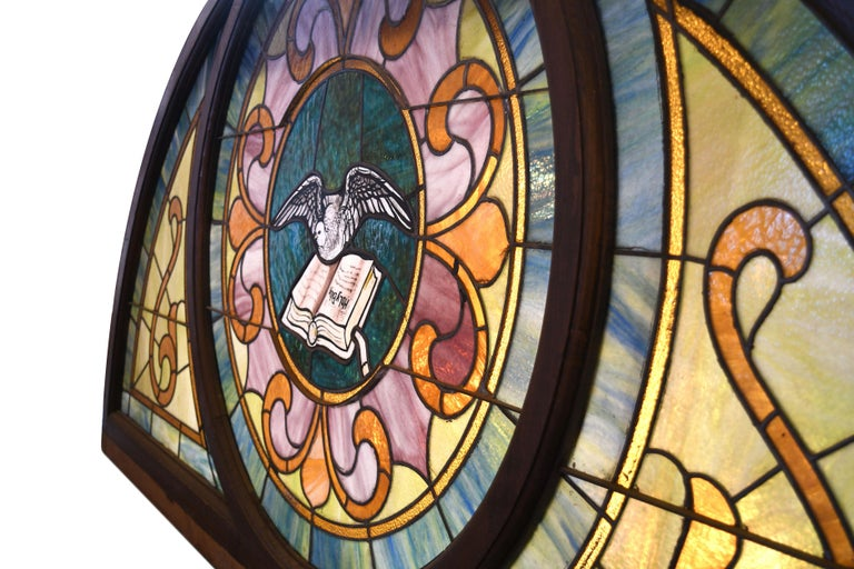 Beautiful pastel colored slag and stained glass window. The green/blue, orange/yellow and pinks all come together to make a soft and peaceful image. The dove and Bible motif at the center is hand painted. It comes together as a whole through organic