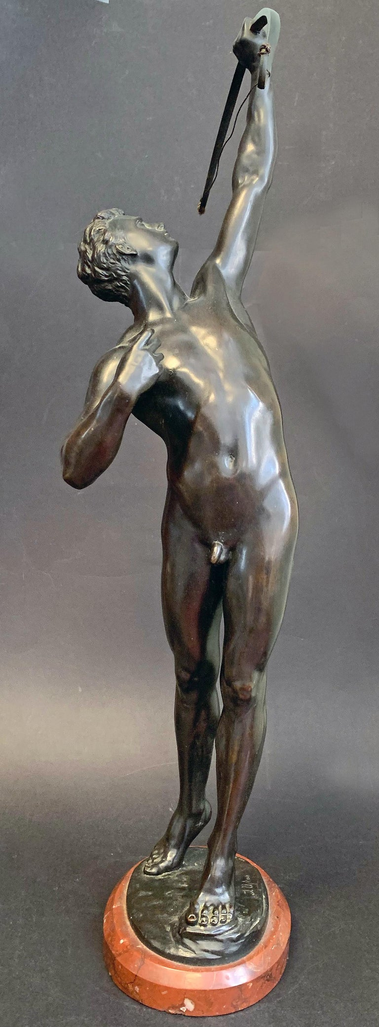 In our opinion, one of the greatest depictions of the male nude in 19th century sculpture, this large bronze by Joseph Uphues depicts a youthful male archer shooting his arrow upwards, no doubt toward a bird overhead. The figure is full of energy