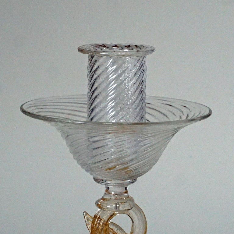 A great Murano candle stick with dolphin sculpture. executed by Archimede Seguso, circa 1960s. clear ribbed glass with gold foil inclusions. Company label on the base.  Measures: Height 9.84