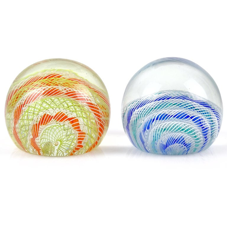 Priced per item (2 available). Beautiful vintage Murano hand blown ribbon design Italian art glass paperweights. Documented to designer Archimede Seguso, circa 1950s. One still retain the original made in Italy labels (blue paperweight). Nice color