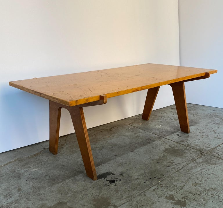 Rectangular cocktail table of cut laminated plywood with solid wood supports. A well-constructed circa 1940s design with an architectural bearing, likely a one-off commission. The top sits within two lateral struts, giving the appearance of bridge