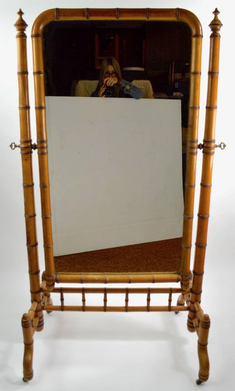 Wonderful architectural Late Victorian cheval mirror by RJ Horner. Solid turned wood faux bamboo frame with original plate glass mirror, and brass turn key hardware. The mirror will tilt to adjust position, the frame is on original brass wheel