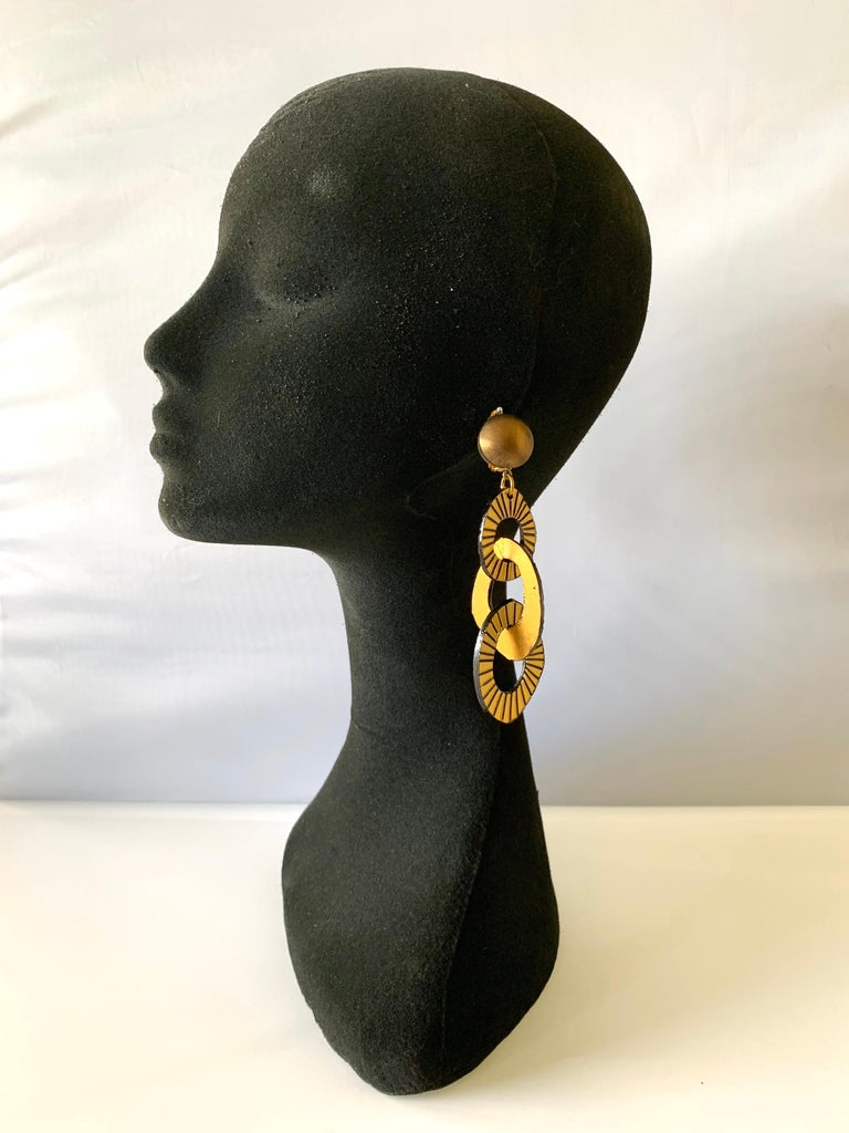 Chic and very current, these handmade fashion-forward artisanal clip-on earrings were made in Paris. The statement earrings feature three carved detailed architectural (enamel and resin composite) geometric links in bronze and gold. Lightweight and