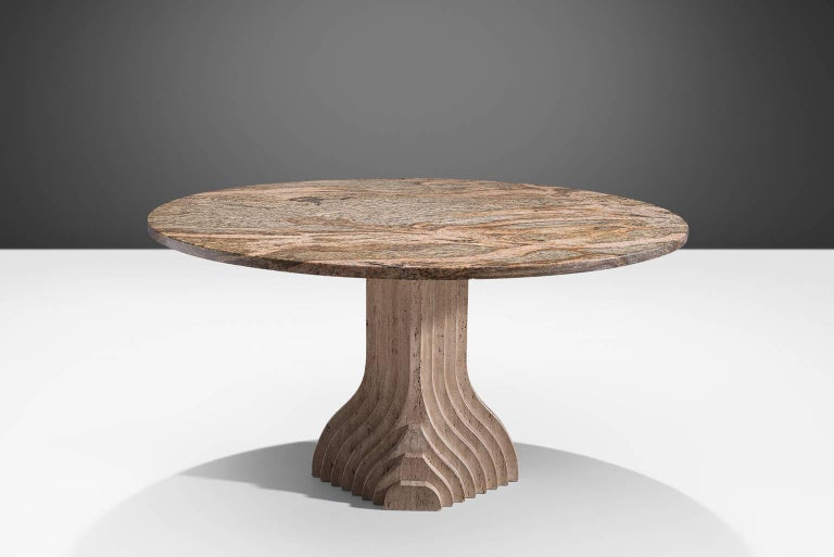 Dining table, travertine and granite, Italy, 1970s  The base of this center table is formed out of a layered pillars that seem exist of several pillars in a row, clearly a reference to the architectural aesthetics of Carlo Scarpa. The circular