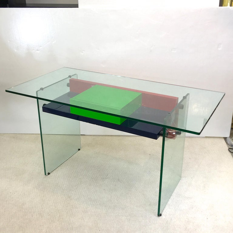 1970s French architectural desk in half inch clear tempered glass with colored high gloss lacquered wood shelf and single drawer. Navy blue, kelly green and red and blackened stainless steel glass standoffs. Kneehole height 23 inches. In the style