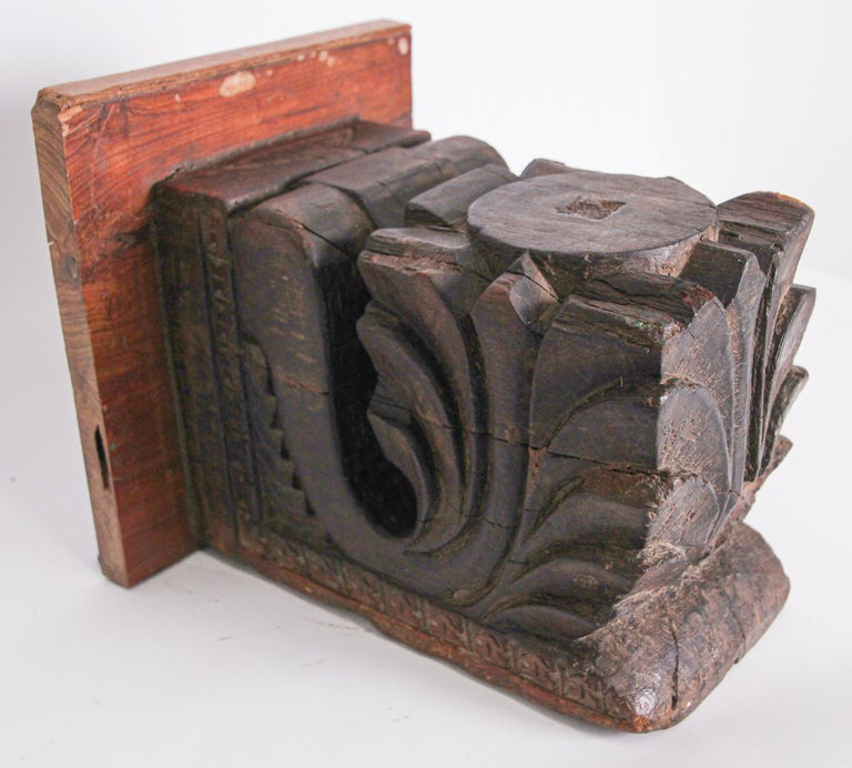 Antique architectural carved wood temple fragment from Rajasthan, India. Made into a wall bracket stand. 19th century Hindu temple fragment. This antique fragment were elements of a section of hand carved wood frieze, within a temple in India.
