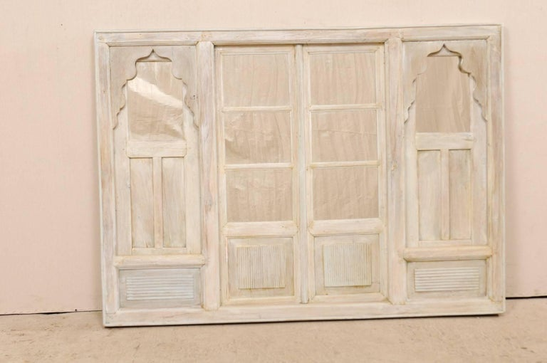 An Indian architectural panel with mirror from the mid-20th century. This vintage architectural panel features a rectangular-shaped frame with four inset doors, each adorn with reeded details, panels, and inset mirrors. Each flanking framed door