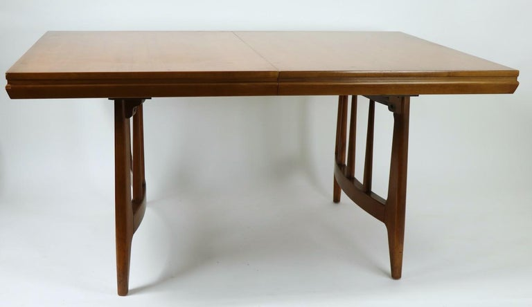 Sharp and crisp design, Mid-Century Modern dining table having opposing semi circular legs and one 12 in leaf. This example is in very fine, clean original condition, ready to use. W with leaf in place 72 in x W without leaf 60 in.