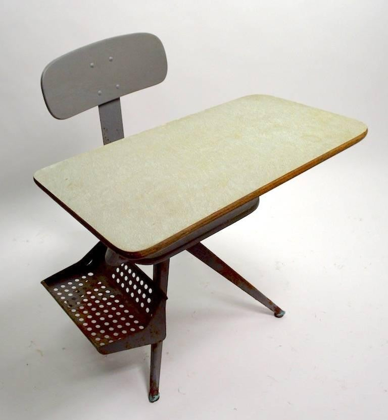 Great architectural design school desk, with obvious Jean Prouve influence. The desk is painted grey metal, with a green tint formica writing surface. Sophisticated style, sculptural form, and high quality commercial construction, will withstand