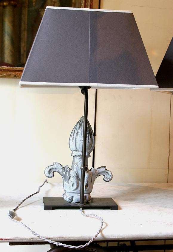 A pair of zinc fleur-de-lis finials made into lamps. The base is bronze, with grey rectangular shades.