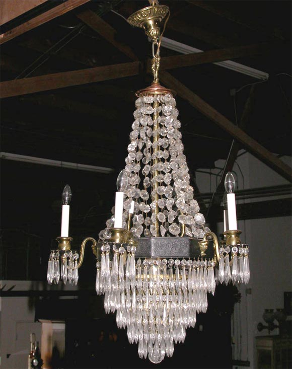 This elegant chandelier is very decorative.  It is made up of many different materials.All the drops are there, the circular band is iron, the cups are brass and it is capped in brass.