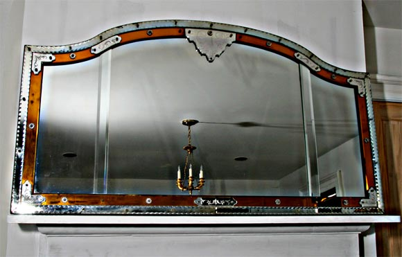 An arched-top Venetian overmantel mirror with amber glass accents. Amber glass is more the color of that in the lighter photos.